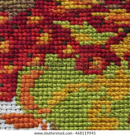 A part of embroidery design, needlework cross stitch. A stitching autumn branch. Closeup, soft selective focus of piece of embroidery