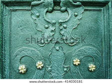 A part of old decorated wrought iron doors. Curved design elements on dark green metal door. Architectural metal background with decorative elements. - stock photo