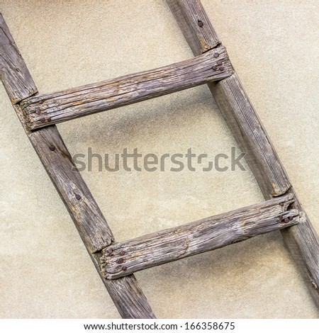 A part of old wooden ladder leaning against a wall. 1x1 - stock photo