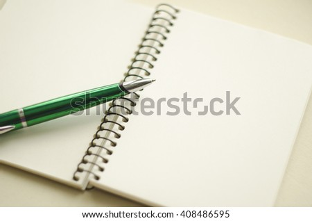 A part of open blank white notebook and green pen on the desk. - stock photo