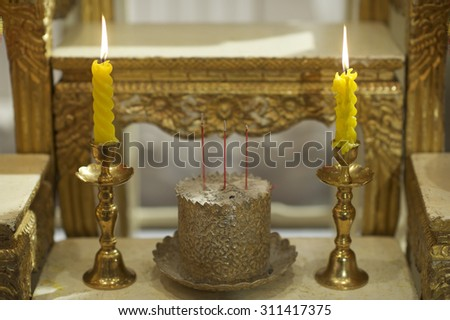 a part of set altar table in thai wedding ceremony, pair of candle and joss-sticks with gold incense containner - stock photo