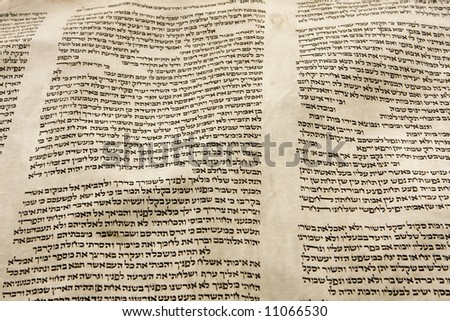 A part of the Hebrew text from a portion of a Torah scroll. This scroll is estimated to be 150 years old and is wrinkled and spotted with age. - stock photo