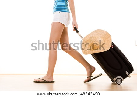 A partial view of a young tourist in summer shorts and sandals, pulling a rolling suitcase.  Theme:  summer vacation or holiday - stock photo