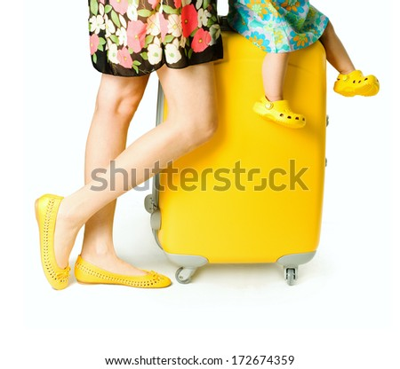 A partial view of a young woman and child in dress, legs with a suitcase on the white background - stock photo