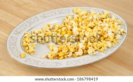 A partially eaten platter of popcorn on a wood dining tabletop. - stock photo