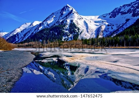 A Partially Frozen Lake with Mountain Range Reflected in the Partially Frozen Waters of a Lake in the Great Alaskan Wilderness. A Beautiful Landscape of Blue Sky, Trees, Rock, Snow, Water and Ice. - stock photo