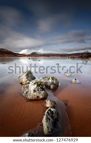 A partially frozen Lochan na h-Achlaise and the Black Mount mountain range, Rannoch Moor near Glencoe - stock photo