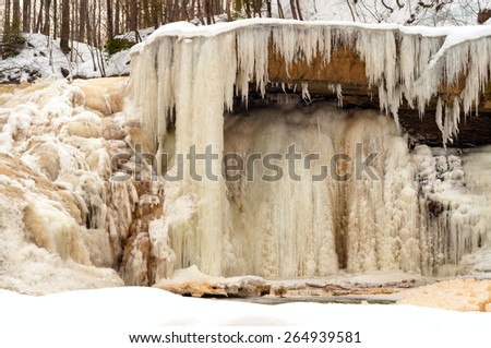 A partially frozen waterfall (the water is running at left) toward the end of winter - stock photo