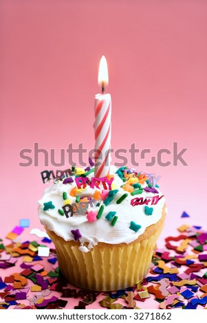 A party cupcake with pink candle and pink background.