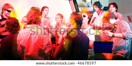 A party on the dance floor in a nightclub in front of the DJ booth. - stock photo