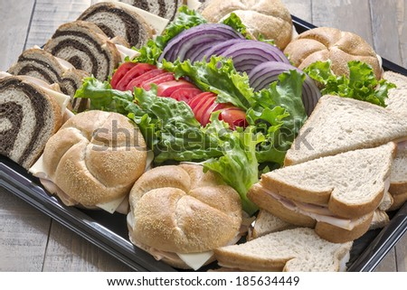 A party platter full of turkey sandwiches made with a variety of breads and served with lettuce, tomato and sliced red onion. - stock photo