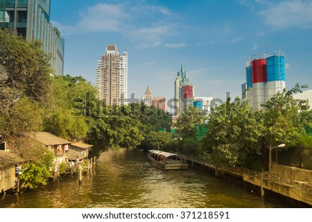 A passenger boat in a klong in the city of Bangkok - stock photo