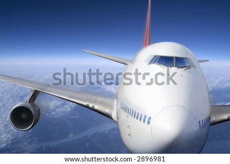 A passenger jet flying high above the clouds. - stock photo