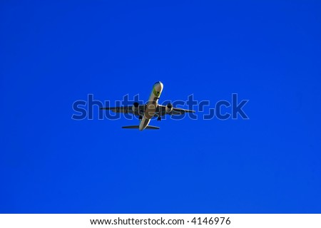 A passenger plane flying high on a blue sky - stock photo
