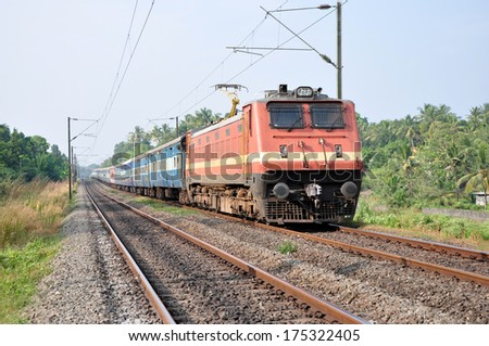 A passenger train being hauled by an electric locomotive in Kerala, India. - stock photo