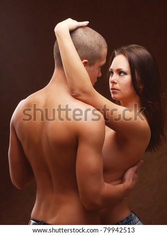 A passionate couple, isolated on brown - stock photo