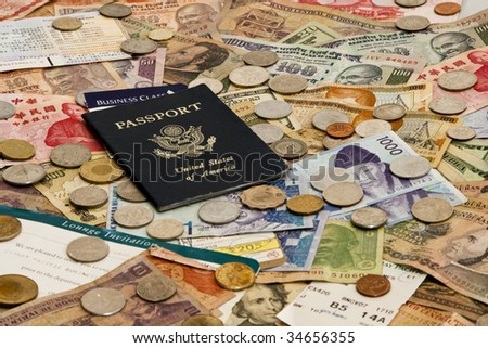 A Passport with ticket stubs on top of mixed foreign money including US, Taiwan, Indian, Hong Kong, Honduran, Malaysian and Korean currency - stock photo