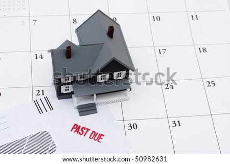A past due bill sitting with a model house on a calendar, Behind on your mortgage payments - stock photo