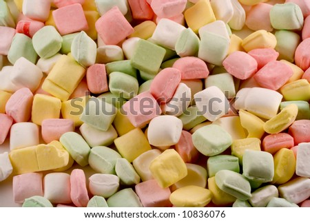 A pastel bed of dinner mints make up this tasty looking background. - stock photo