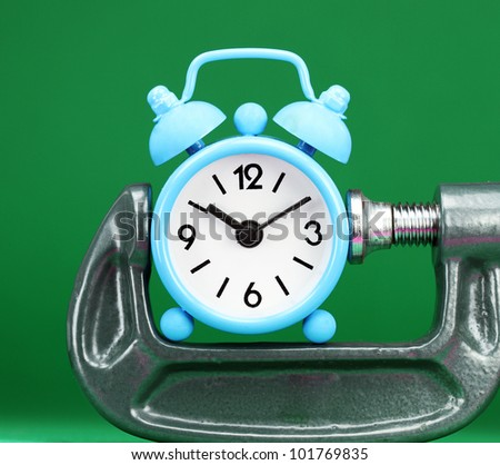 A pastel blue colored  alarm clock placed in a Grey clamp against a pastel blue background, asking the question do you manage your time effectively. - stock photo