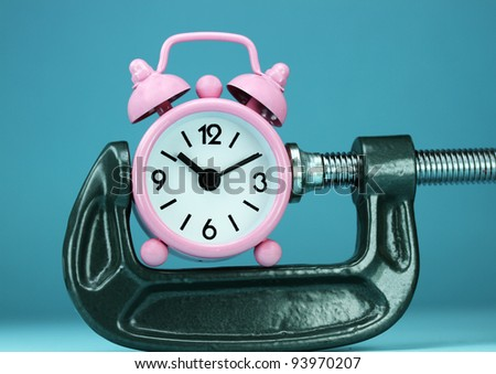 A pastel pink alarm clock placed in a Grey clamp against a pastel purple background, asking the question do you manage your time effectively. - stock photo