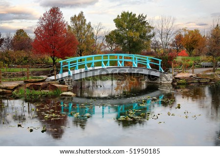 A Pastoral Scene Of A Japanese Foot Bridge Over A Quiet Little Pond On A Rainy Day In Autumn - stock photo