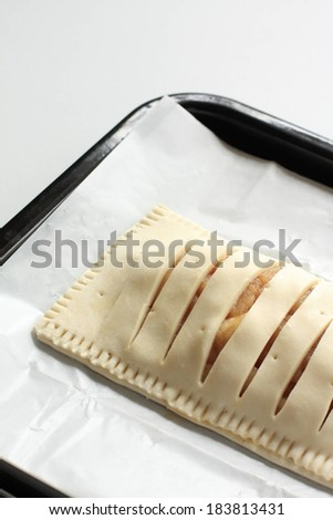 A pastry sitting on a baking sheet to be baked. - stock photo