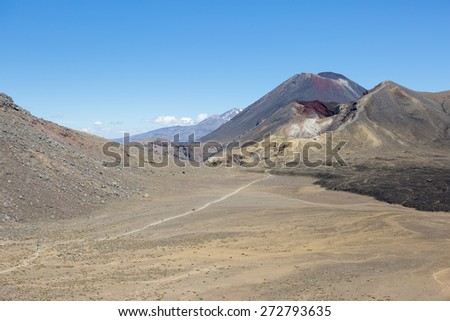 A path leading from Mount Ngauruhoe over the Red Crater to the Blue lake with Mounts Ruapehu in the back - stock photo