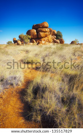 A path leads through the low scrub to a large pile of rocks in the Australian outback.