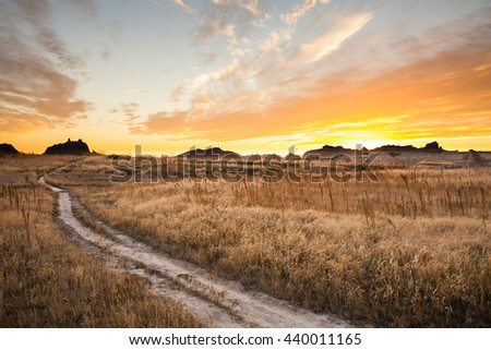 A Path though Badlands National Park at sunset. - stock photo
