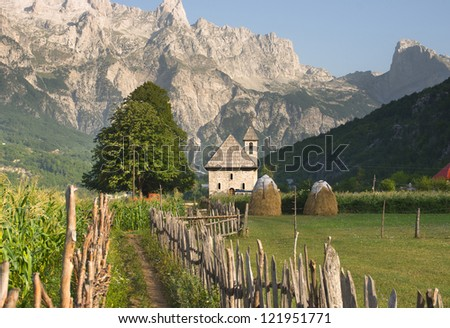 a path with wooden fence leads the catholic church in the Theth Valley, on background the mountains of Albanian Alps - stock photo