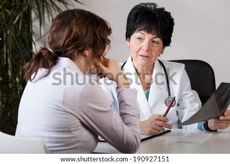 A patient and a doctor analyzing the outcome of an examination - stock photo