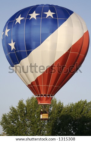 A patriotic hot air balloon lifts off into the blue sky - stock photo