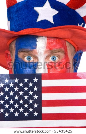 A patriotic man with red, white and blue face paint holds up an American flag. - stock photo