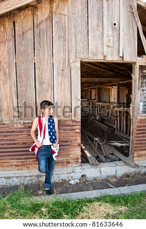 A patriotic teenager leaning against an old abandoned barn while holding an American flag. - stock photo