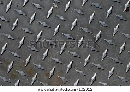 A pattern formed by diamond deck sheet metal. - stock photo