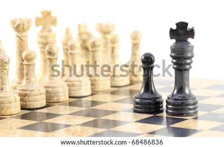 A pawn and his king face off against the entire army of opposing chess pieces. - stock photo
