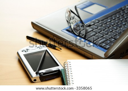 A PDA, notebook and laptop in a typical business environment setting - stock photo