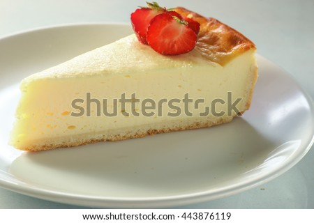 A peace of cheesecake with strawberry sauce on white background