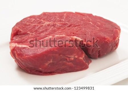 a peace of raw filet beef on a white background