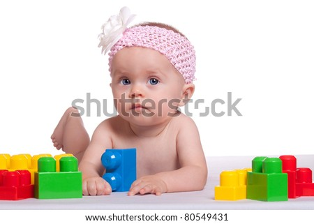 A peaceful image of an infant playing with plastic blocks. - stock photo