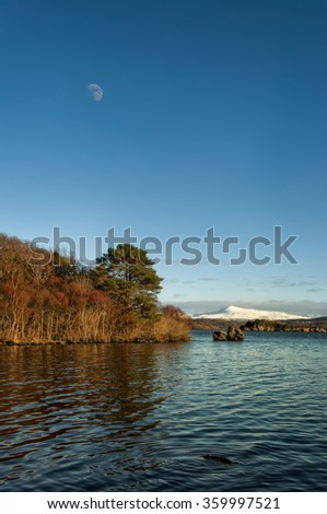 A peaceful lake shore landscape with the Moon and a distant snowy mountain - stock photo