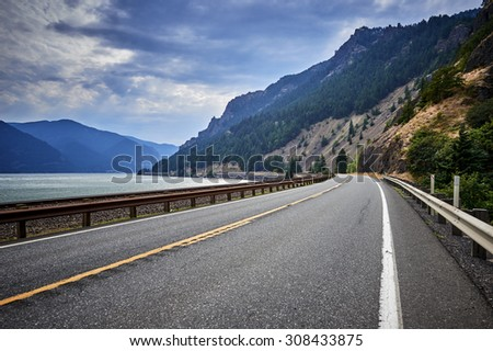 a peaceful mountain road in the summer - stock photo