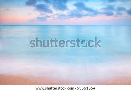 A peaceful scene of a calm ocean and sunset - stock photo