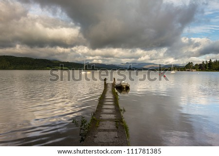 A peaceful stone jetty on Lake Windermere wth the Langdales in the background - stock photo