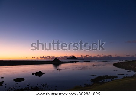 A peaceful, winter evening at the Whakatane River mouth in New Zealand. This stunning and colorful photo of Whale Island and the Bay of Plenty would be great for many various ideas and concepts. - stock photo