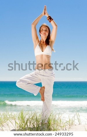 A peaceful young woman doing yoga on the beach - stock photo
