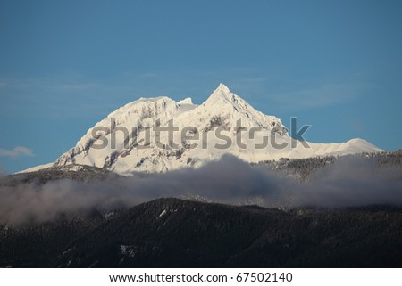 A peak freshly covered in snow in the coastal range between squamish and whistler. - stock photo