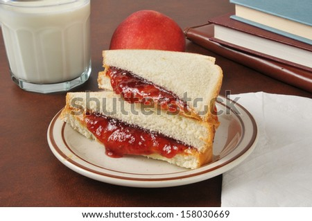 A peanut butter and jelly sandwich with an apple, a glass of milk and school books - stock photo