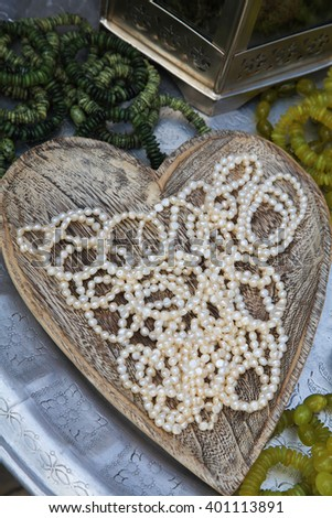 A pearl necklace in a wooden heart shaped bowl